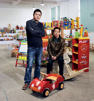 Father and son surrounded by wooden toys made by their factory